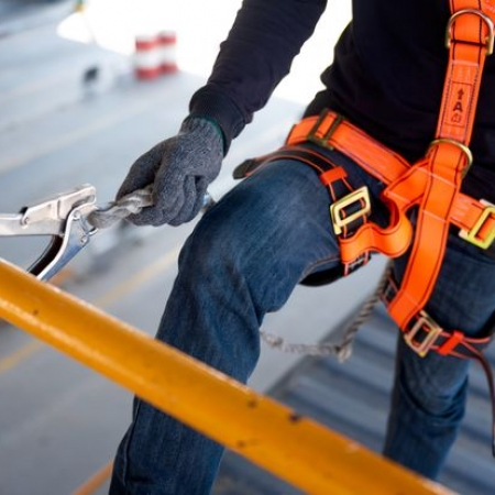 Construction worker use safety harness and safety line working on a new construction site project.